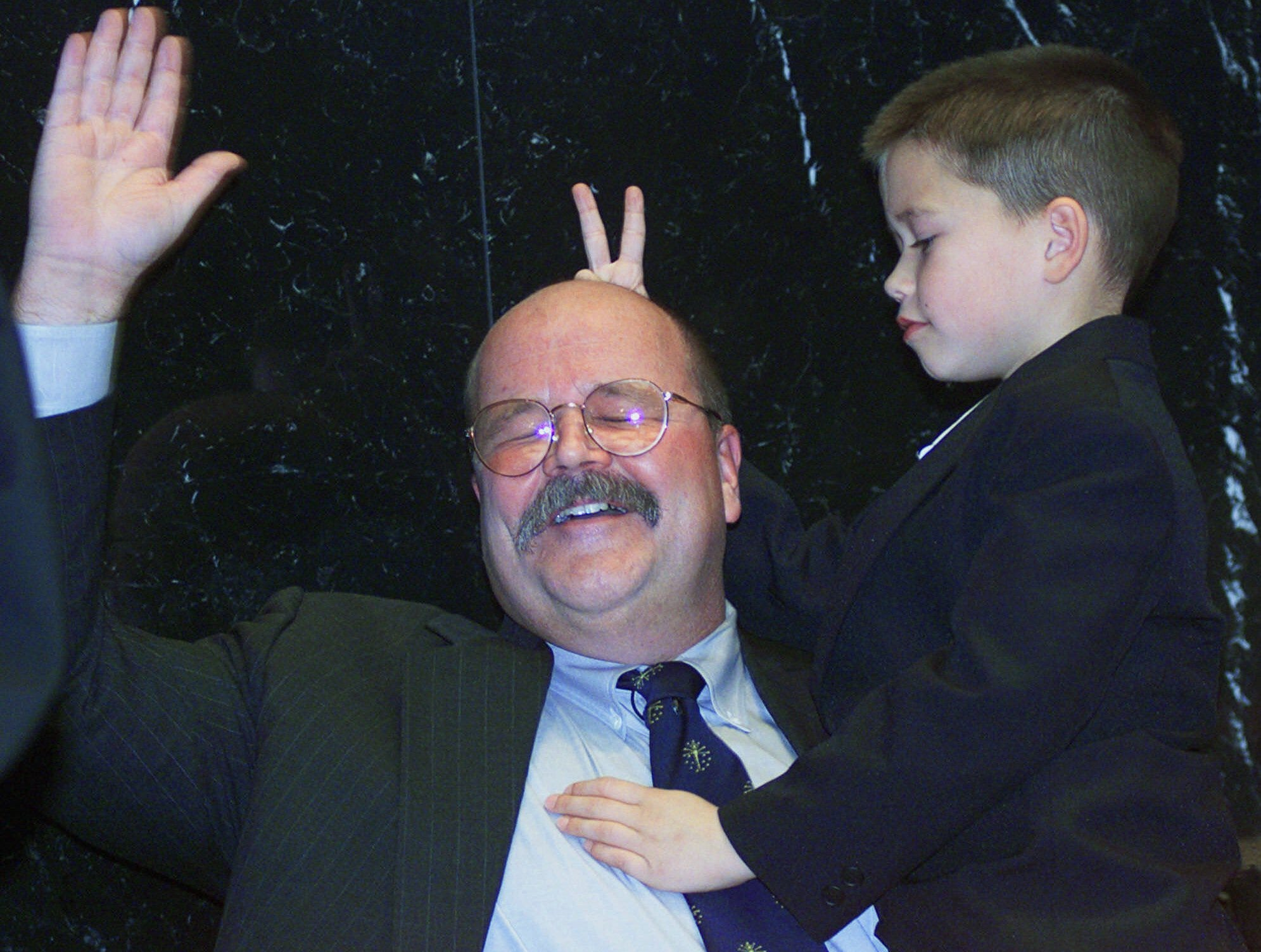"John R. Gregg D-Sandborn being sworn in as Indiana House Speaker in the Statehouse Tuesday Nov. 21 2000 gets the ""rabbit ears"" from his youngest son Hunter 7 to begin the 112th General Assembly on Organizational Day. The good natured Gregg calmly went on with the ceremony and made it ""Kids Day"" at the podium. (AP Photo/Chuck Robinson)"