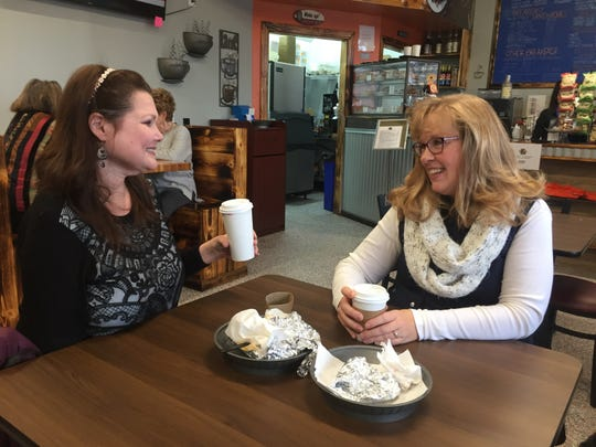 Two customers talk over cups of coffee at Best Friends Coffee & Bagels in Brownsburg.