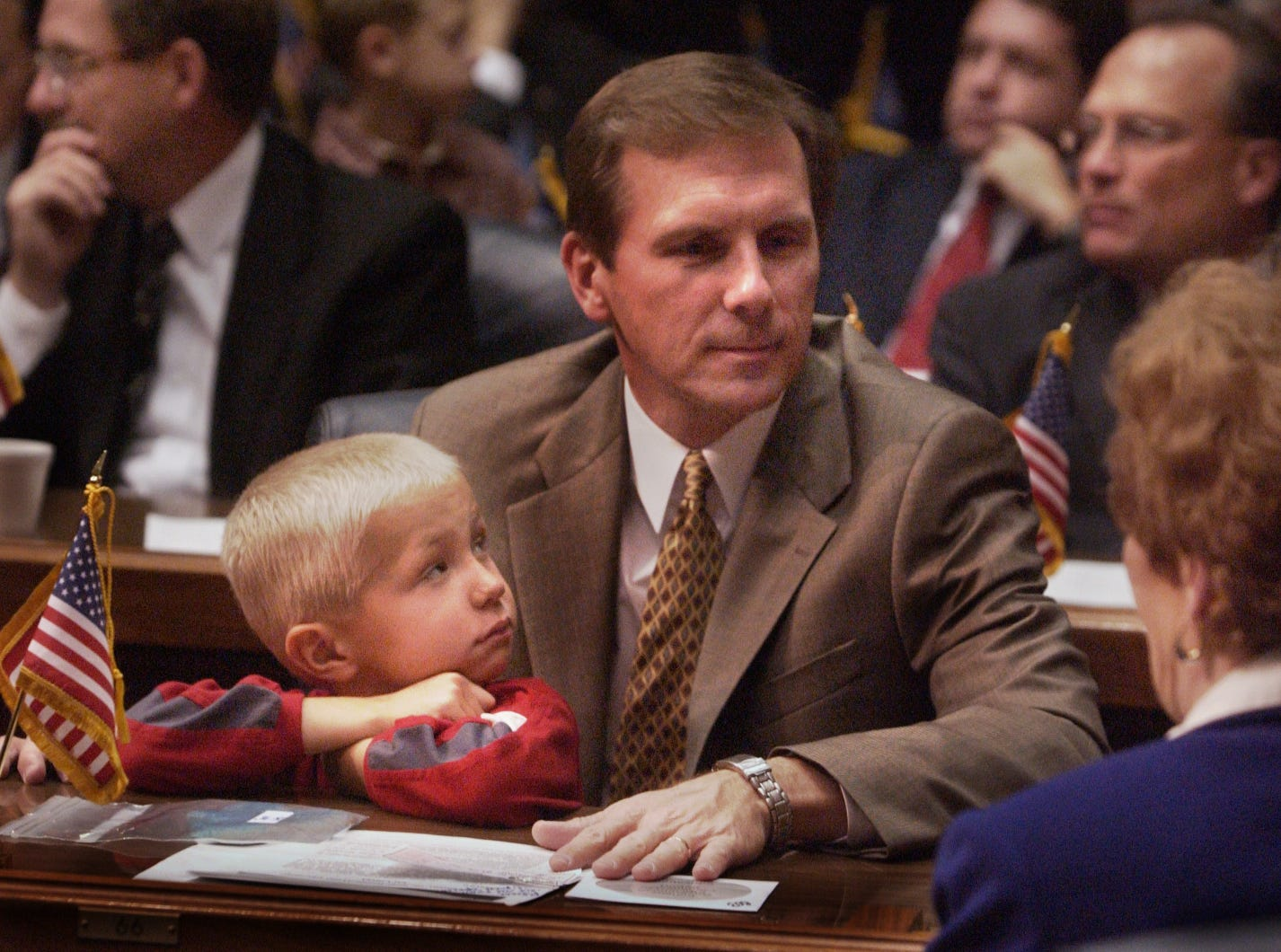 Jared Ripley, 5,  watches his dad, Representative, Mike Ripley (R-Monroe), who is chatting it up with fellow rep, Vaneta Becker (R-Evansville) in 2004.