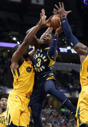 Indiana Pacers guard Aaron Holiday (3) drives on and is fouled by Utah Jazz forward Derrick Favors (15) in the second half of their game on Monday, Nov. 19, 2018. The Pacers defeated the Jazz 121-94.
