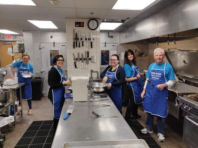 Hills Bank volunteers work in the Shelter House kitchen preparing meals on Friday, Nov. 16.