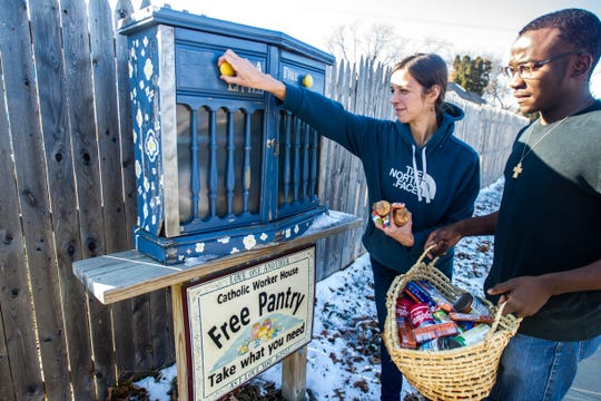 Emily Sinnwell, left, and Patrick Mbiya restock a free pantry on Tuesday afternoon, Nov. 20, 2018, outside the Catholic Worker House along Sycamore Street in Iowa City.