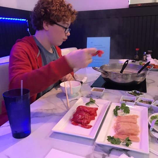 John Kilgore selects a piece of thinly sliced beef to add to a simmering pot of broth at Dragon Hotpot in Ridgeland.