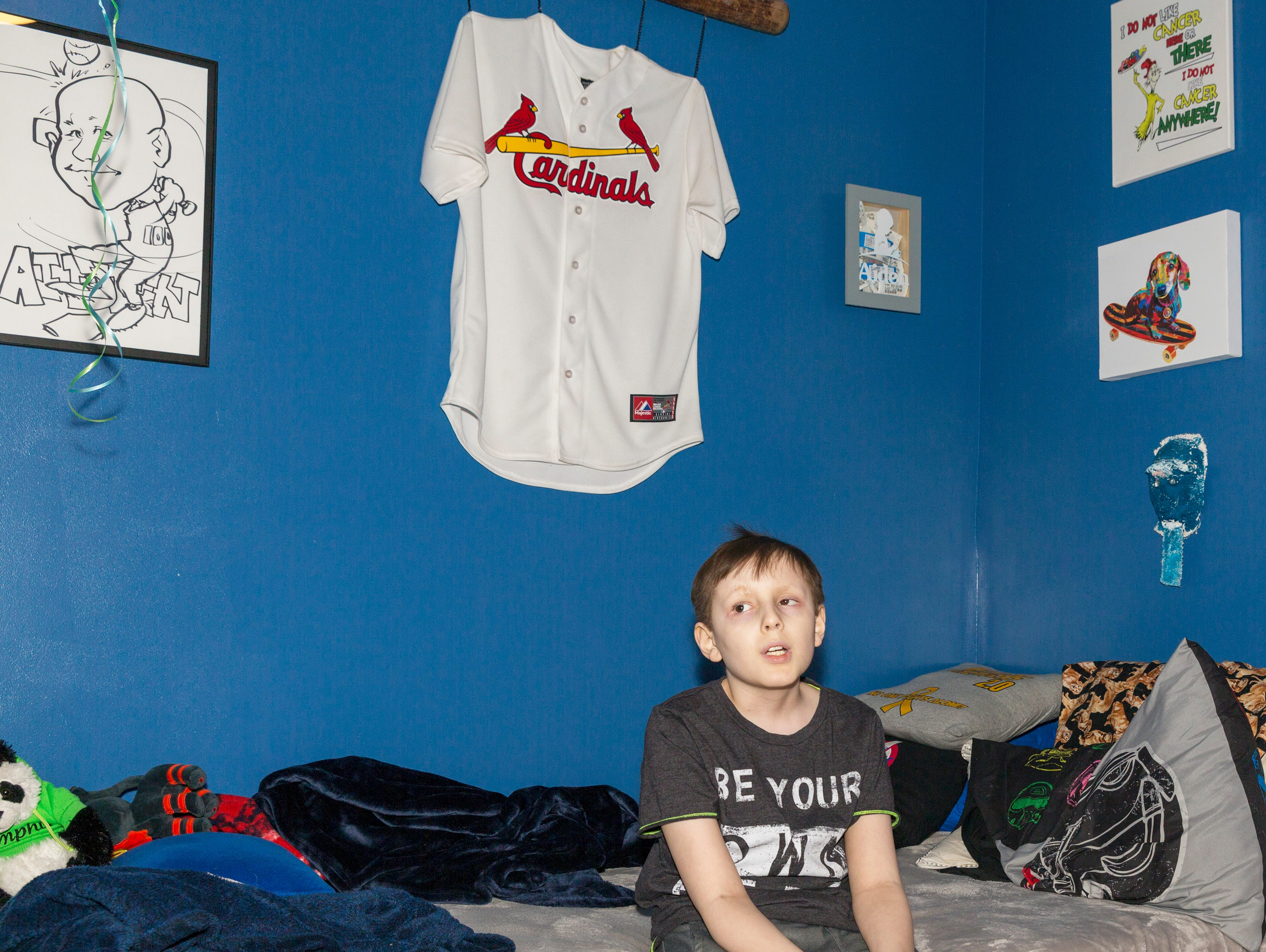 Aiden Taylor sits on his bed at his family's home in Jackson, Tenn. His walls are adorned in artwork and mementos, including a blue paper-mache mask he made in school.