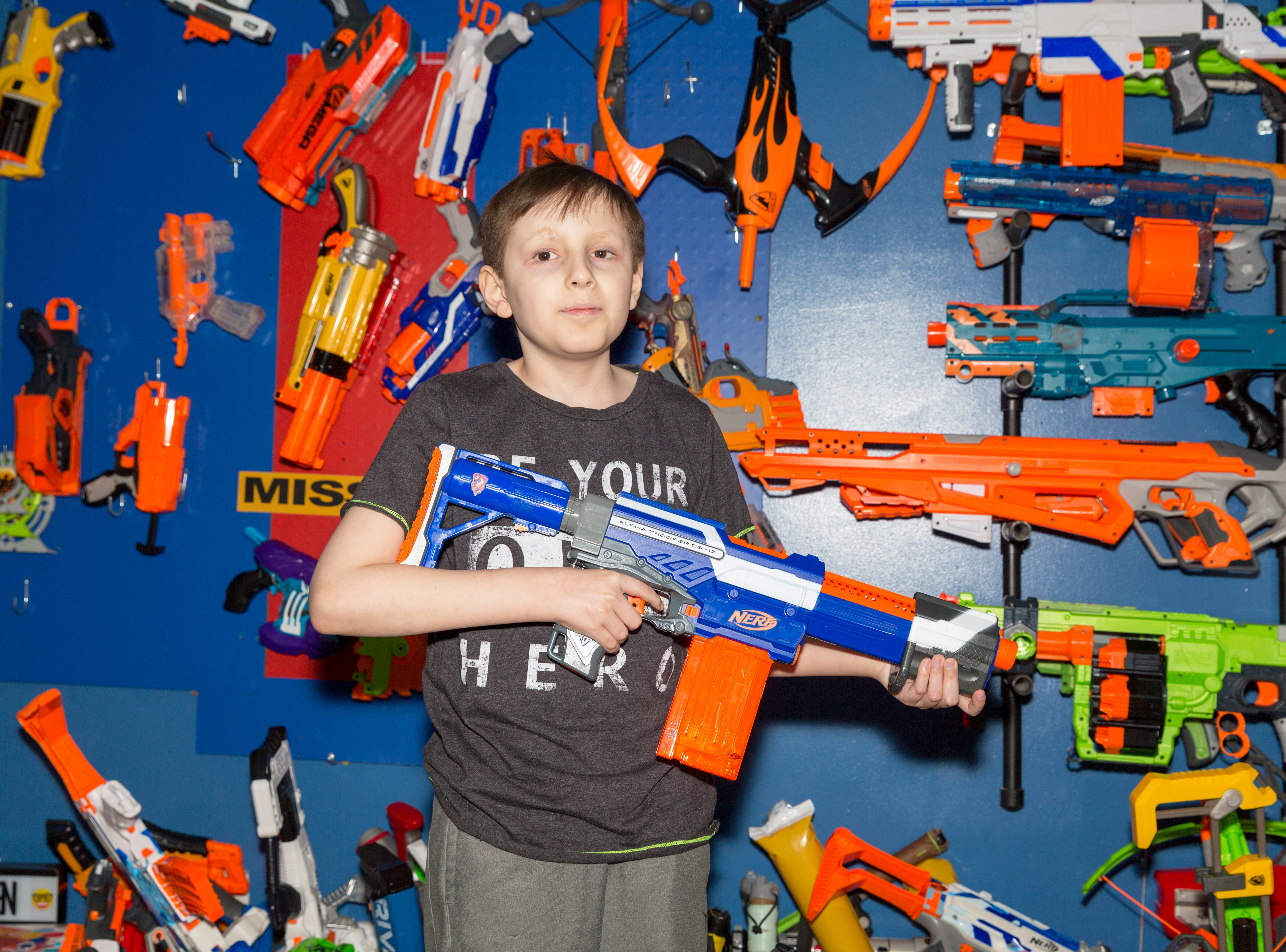 Aiden Turner, 13, poses with his favorite Nerf gun in his room in his family's home in Jackson, Tenn. Aiden has about 100 Nerf guns, his parents Lisa and Josh said, and he knows the names of all of them.