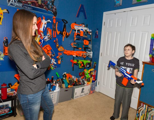 Aiden Taylor talks with his mother Lisa Taylor in his room in his family's home in Jackson, Tenn.
