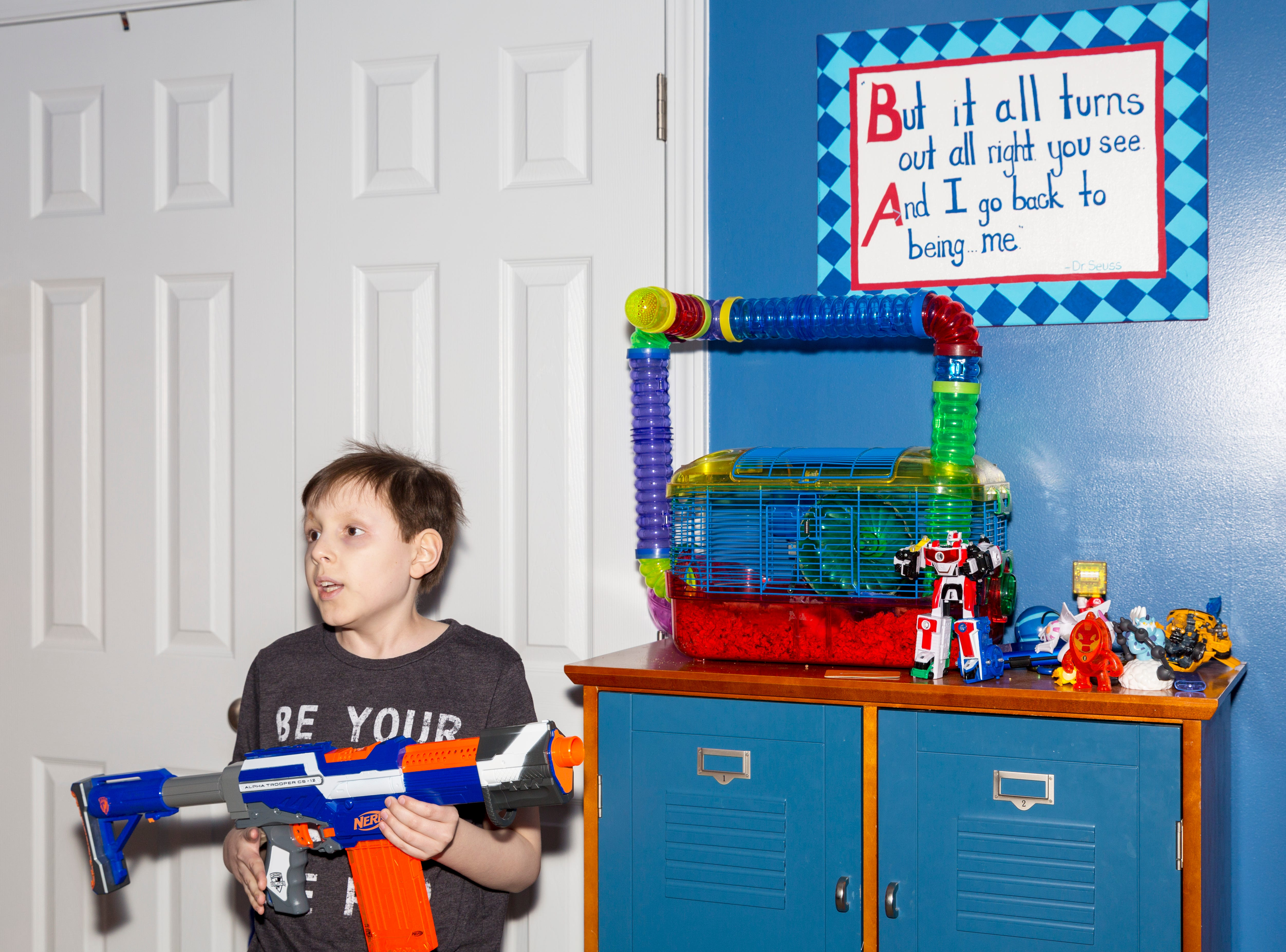 Aiden Taylor stands in front of his hamster Elsa's cage holding his favorite Nerf gun in his family's home in Jackson, Tenn. A few Dr. Seuss quotes decorate his room, including this one.