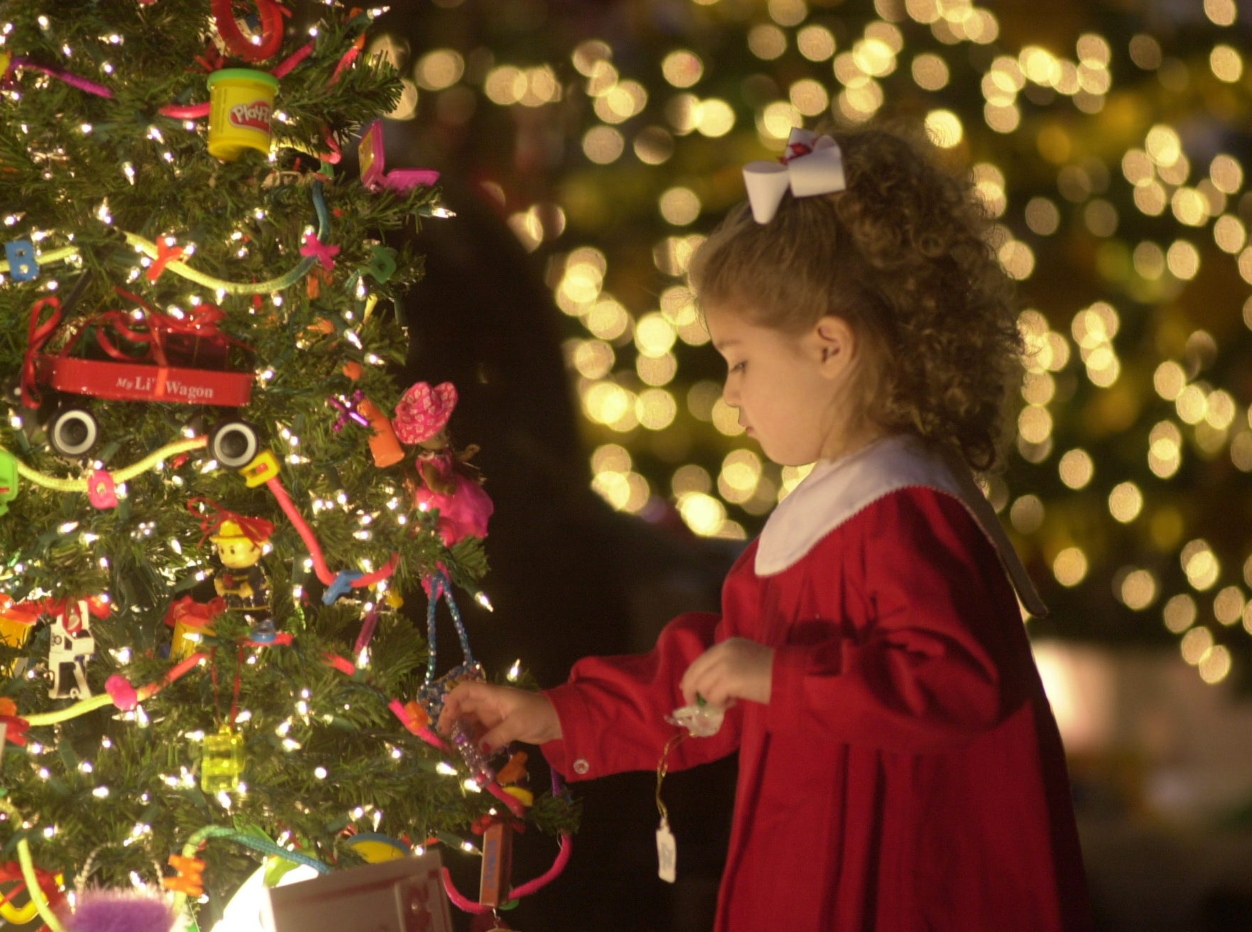 Megan Strader, 3, of Morristown plays with some ornaments on a Christmas tree donated by the Fair Garden Family and Community Service Center while attending the 2004 Fantasy of Trees at the Knoxville Convention Center Saturday.  JEFF ADKINS/NEWS SENTINEL STAFF