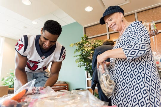 LaTroy Lewis, linebacker for the Tennessee Titans and former UT Vol, and a patient sort hats at MD Anderson Cancer Center in Texas, March of 2018.