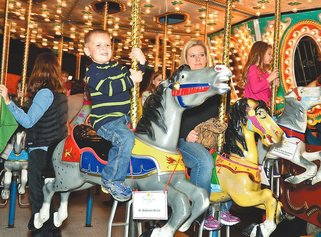 Evan Rivera rides the carousel at the 2014 Fantasy of Trees.