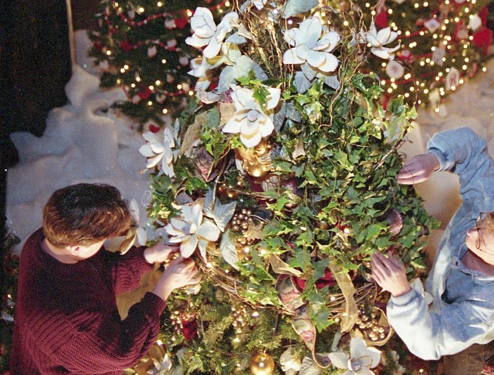 Douglas Bates, left, and Malcom Byrd of Tis the Season Designers decorate a Christmas tree at Fantasy of Trees, November 1993.