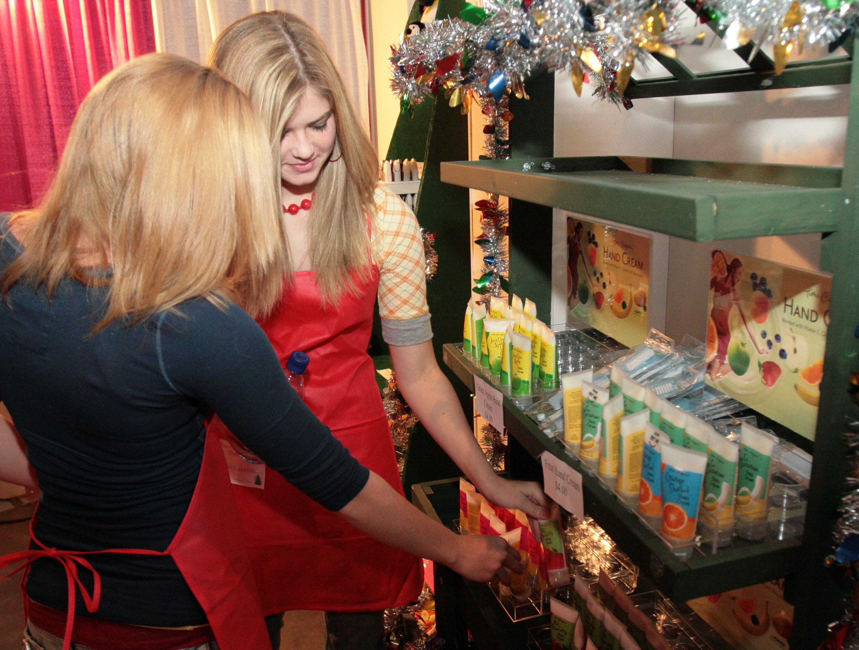 Volunteers Victoria McCauley, 16, left, and Hayley Jensen, 14, stock the selves in the Secret Santa shop at the Fantasy of Trees on Friday at the Knoxville Convention Center.   Photo special to the News Sentinel by Chad Greene