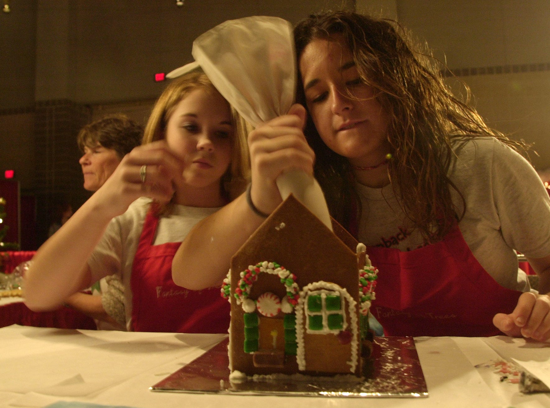 Greenback High School students Crysta Hill, left, and Raven Vogt demonstrate how to make gingerbread houses during the 2004 Fantasy of Trees at the Knoxville Convention Center Saturday.  JEFF ADKINS/NEWS SENTINEL STAFF
