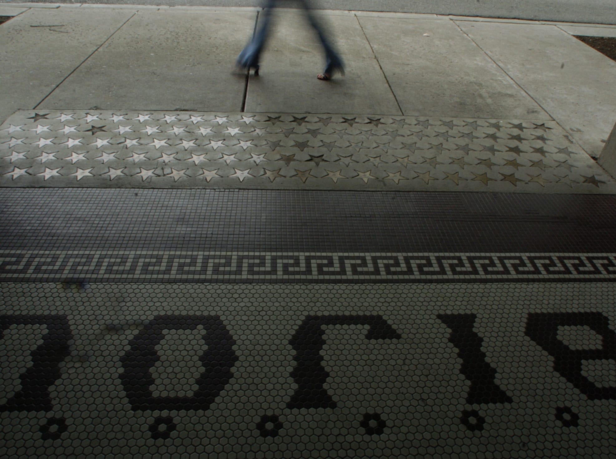 A pedestrian walks past the tile floor at the front of the Bijou Theatre in downtown Knoxville Tueseday afternoon.  6/4/2004