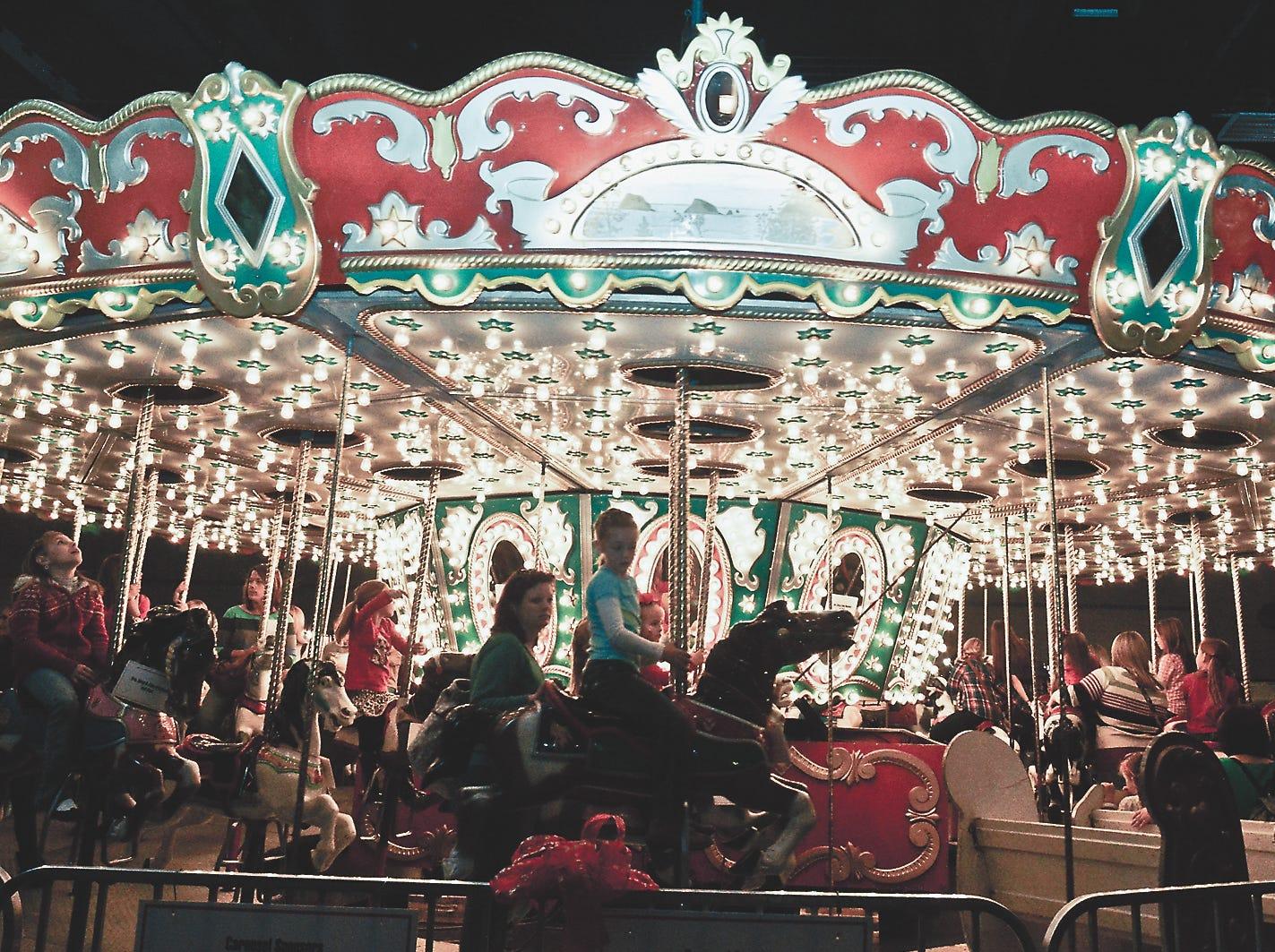 Guests at Fantasy of Trees ride the carousel, November, 2012.