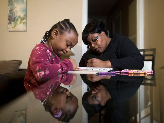 Vanicia Vance and daughter Z'niyah spend time at home Monday, Nov. 19, 2018, for an evening of coloring. Vance is a single mother who works in home health care and is attending college. She is receiving an Empty Stocking Fund basket this year.