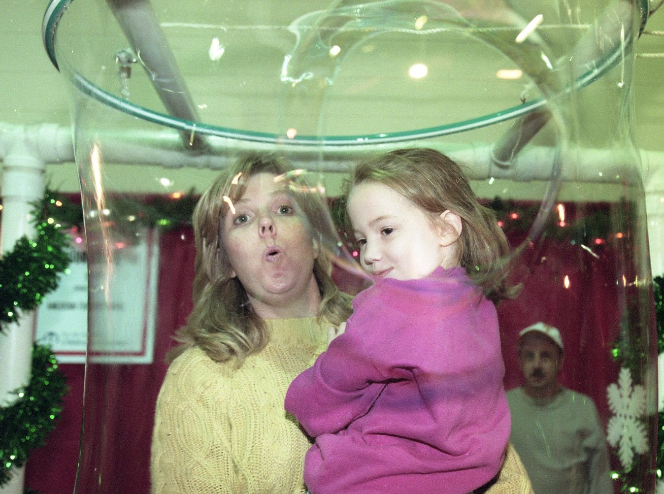 Susan and Samantha Calabrese blow a hole in a large bubble while at Fantasy of Trees, November, 1998.