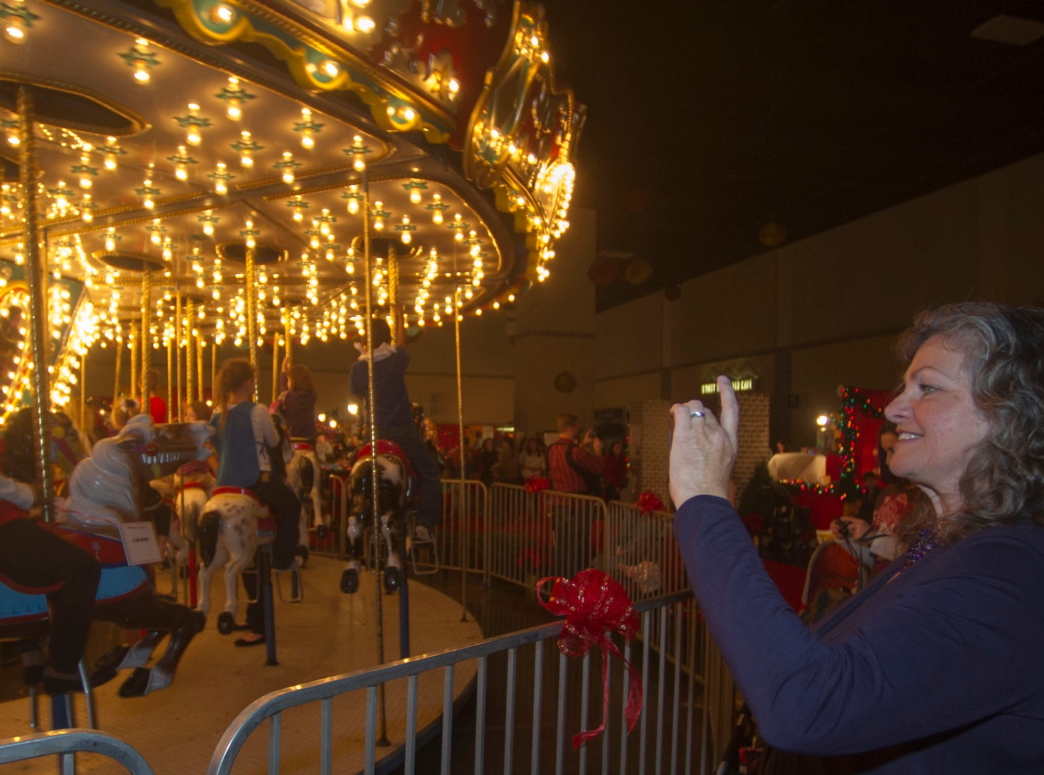 Ailene Radcliffe, right photographs her grand child riding the carousel at the Fantasy of Trees. The 28th Fantasy of Trees once again transforms the downtown Knoxville Convention Center into a winter wonderland of decorated trees, gingerbread houses, holiday shops and children's activities, helping move Thanksgiving week into the Christmas season. ( J. MILES CARY/NEWS SENTINEL )