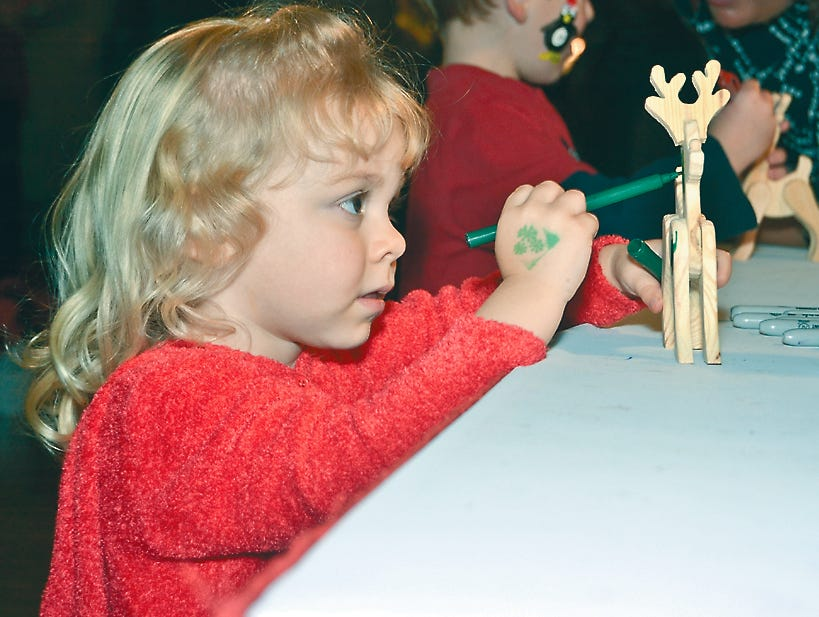Kennedy Tull decorates a wooden reindeer at Fantasy of Trees, November 2011.