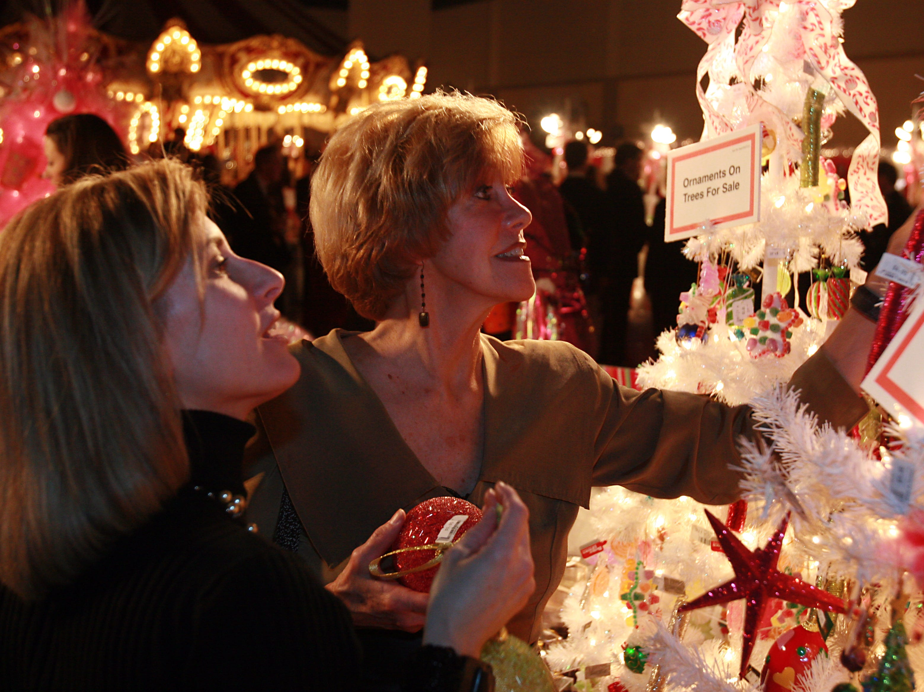1126peop.BC#6768--LIVING--Wendy Hall, left, and Gale Hinton peruse through ornaments for sale at the Knoxville Convention Center on Tuesday, November 21.  The Convention Center hosted the Fantasy of Trees opening Gala to benefit Children's Hospital.  (Bryan Campbell/ Special to the News Sentinel)