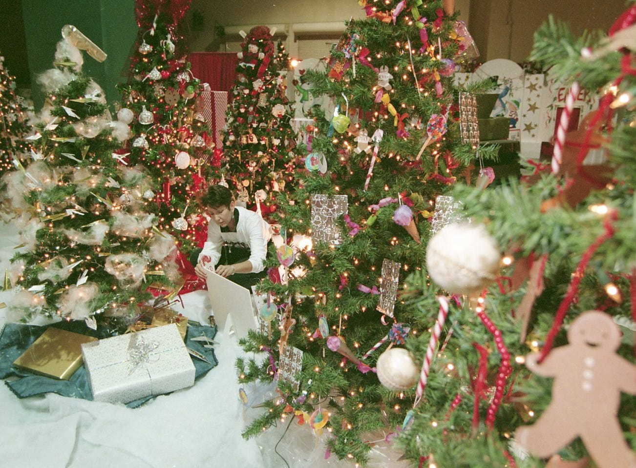 Sandy McKelvy, co-shair of Fantasy of Trees, adjust as sign among the many decorated trees, November, 1997.