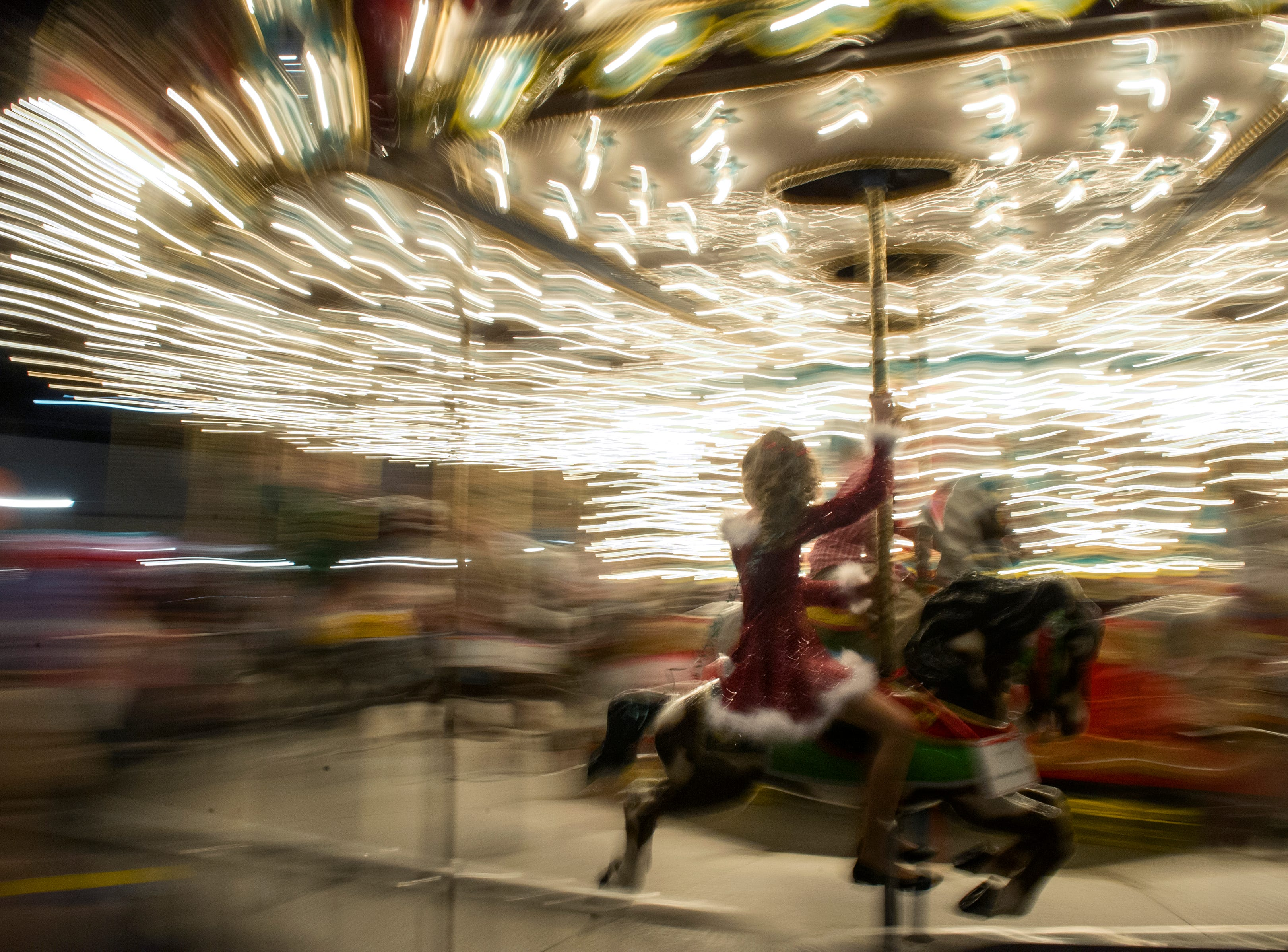 A girl dressed in Christmas attire rides the carousel during the Fantasy of Trees at the Knoxville Convention Center Wednesday, Nov. 25, 2015. (JESSICA TEZAK/NEWS SENTINEL)