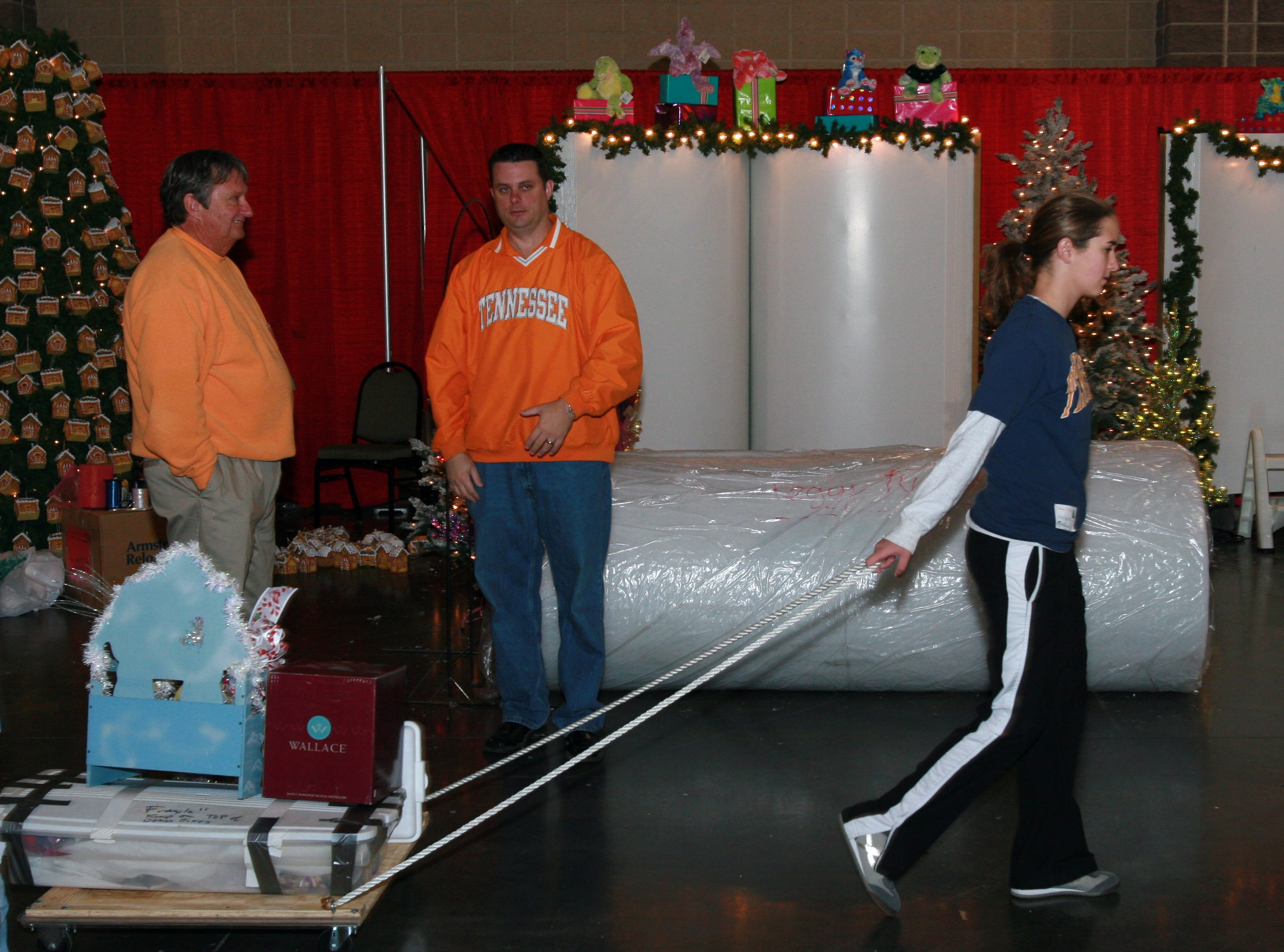 fantasy3.BC#6759--LIVING--Molly Broome(16), a member of the Bearden High Key Club, helps to load in supplies for a vendor at the Knoxville Convention Center on Saturday, November 18.  Broome was among many teenage volunteers who turned out to  volunteer their time to make the Fantasy of Trees a success.  (Bryan Campbell/Special to the News Sentinel)