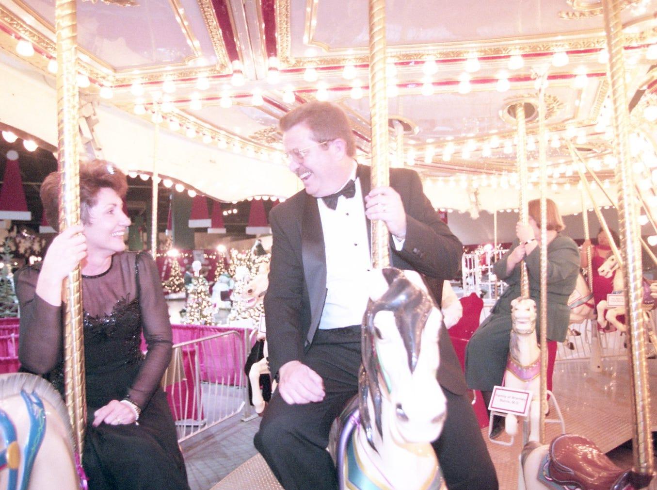 Sandy McKelvy and Cleston Jones ride the merry-go-round at Fantasy of Trees, November, 1997.