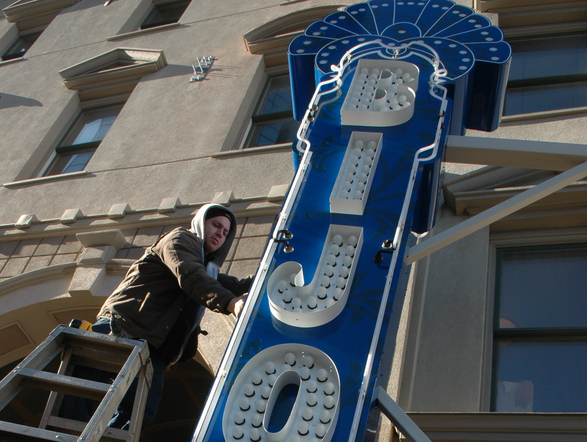 Jordan Cooper of Signco Incorporated of Knoxville attaches the electrical access panels to the new blade sign for the Bijou Theater Thursday morning. The sign will be introduced to the public on Wednesday, Jan. 28 at a ceremony in front of the theater hosted by  Bijou board president Larsen Jay with the flipping of a giantswitch to light the new sign and marquee. Thursday, January 22, 2009