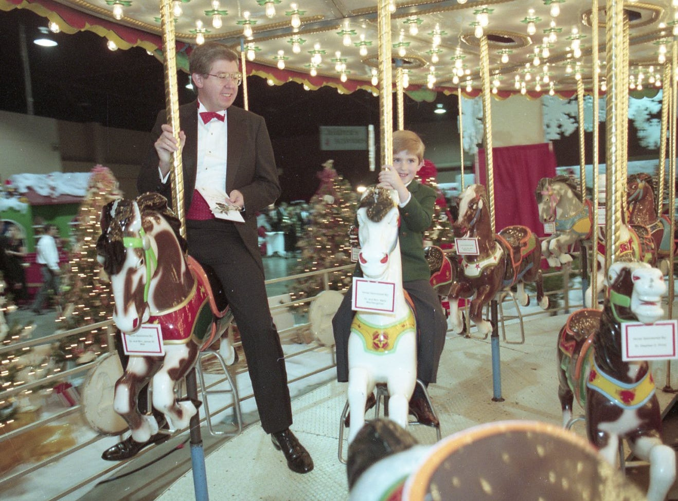 Bob Cross enjoys a ride on the carousel with his son, Matthew, on opening night of Fantasy of Trees, November, 1994.