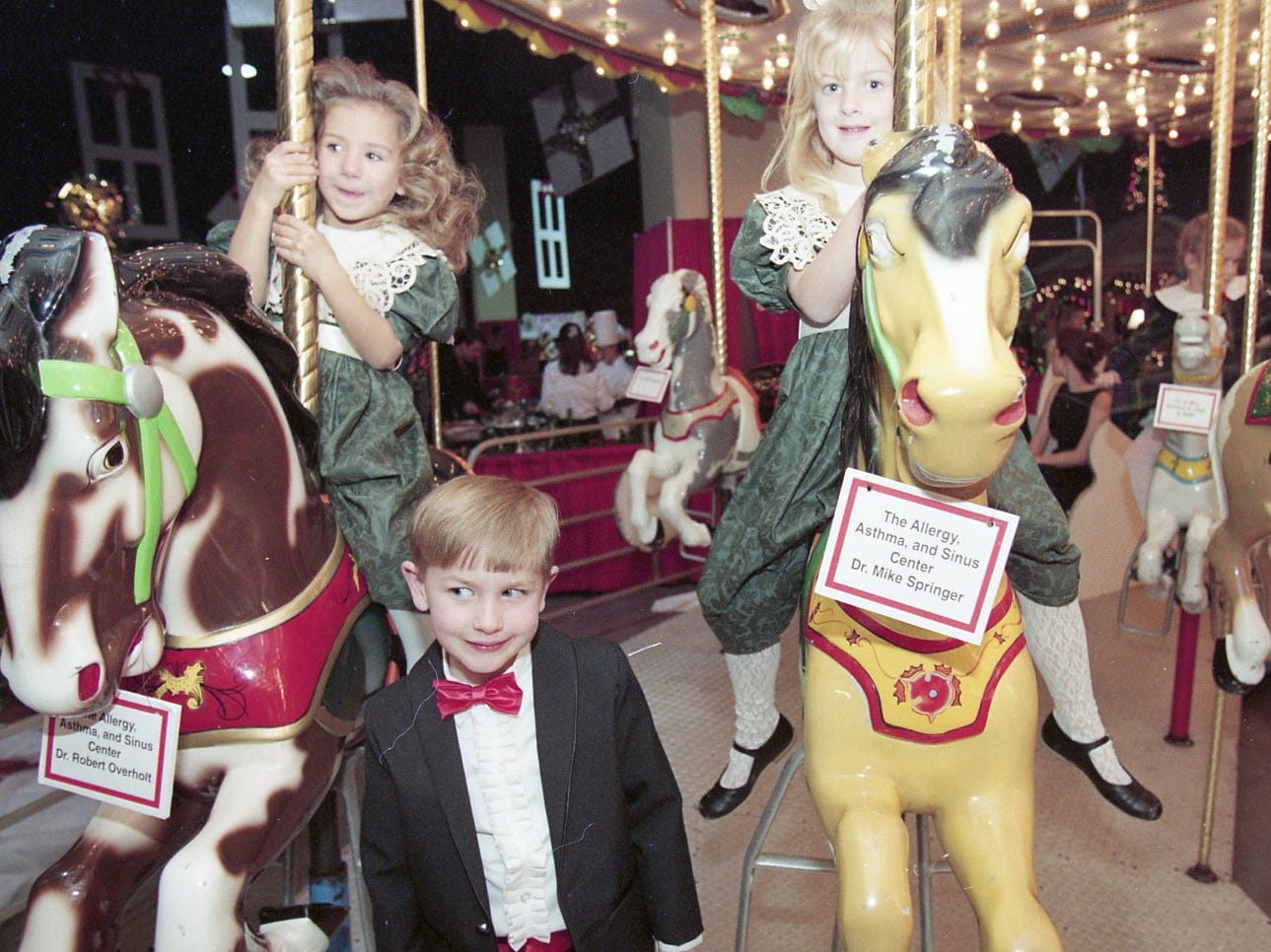 Abbey and Adam Kerley and Holland Talbott ride the merry-go-round at Fantasy of Trees, 1995, opening night gala.