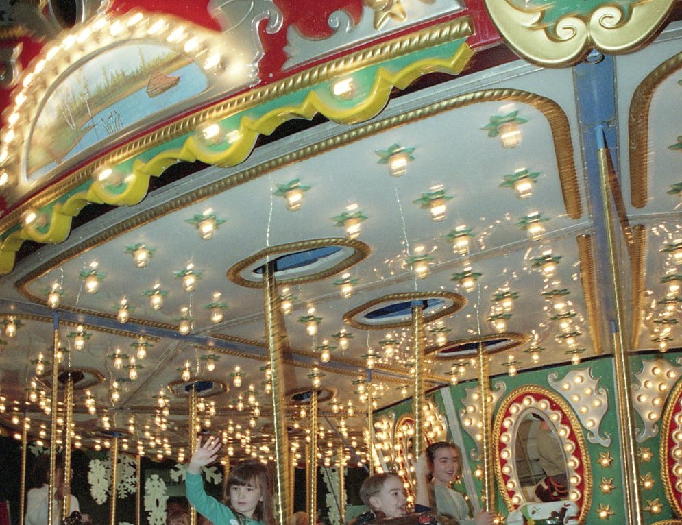 Alicia Mink of Blaine, TN waves to friends from the merry-go-round at Fantasy of Trees, November 1992.