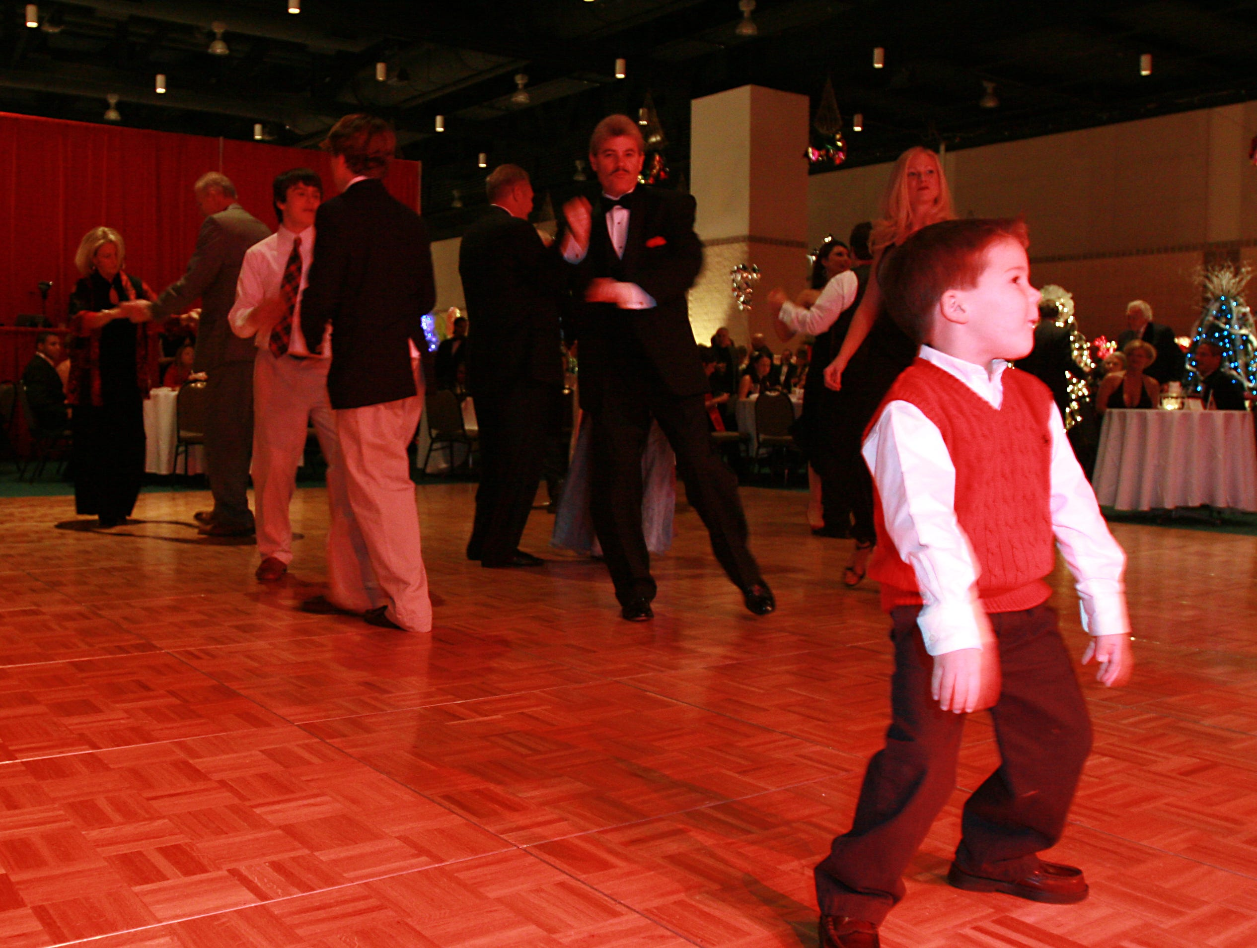 1126peop4.BC#6768--LIVING--Patrick Boles (5) along with parents Debbie and Pat Boles (Not Pictured) gets down on the dance floor at the Knoxville Convention Center on Tuesday, November 21.  The Convention Center hosted the Fantasy of Trees opening Gala to benefit Children's Hospital.  (Bryan Campbell/ Special to the News Sentinel)