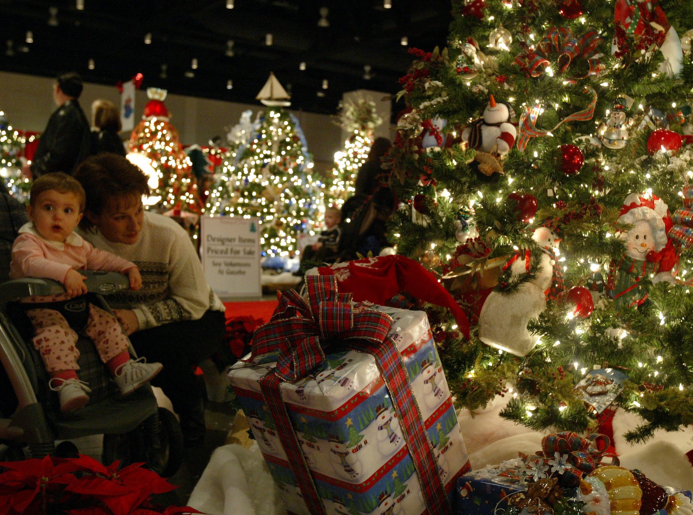 fantasyoftrees2.CC#2540.jpg---living----Nikki Stacy of Seymour and her daughter Savannah take in the bright lights of the Christmas trees during the Fantasy of Trees held at the Knoxville Convention Center.Photo by Cathy Clarke, Knoxville News Sentinel11/28/04