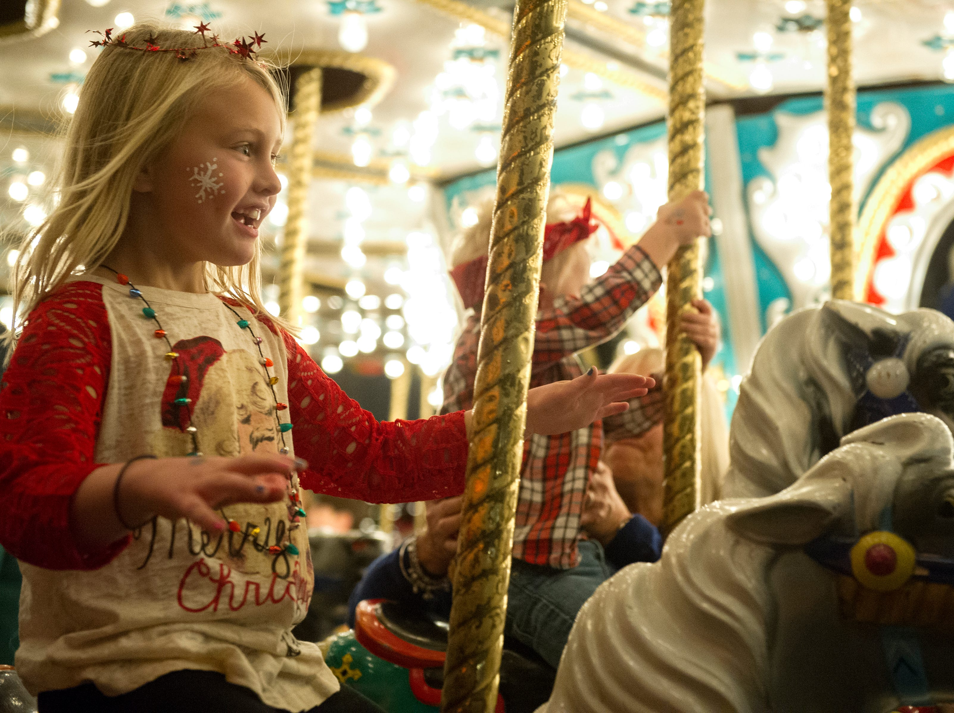 A girl rides the carousel with no hands during the Fantasy of Trees at the Knoxville Convention Center Wednesday, Nov. 25, 2015. (JESSICA TEZAK/NEWS SENTINEL)