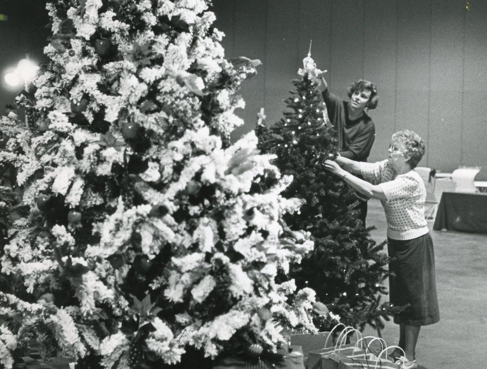 Laura Howard, left, and Jane Boyd decorate the featured tree at the Fantasy of Trees benefit, November, 1985.