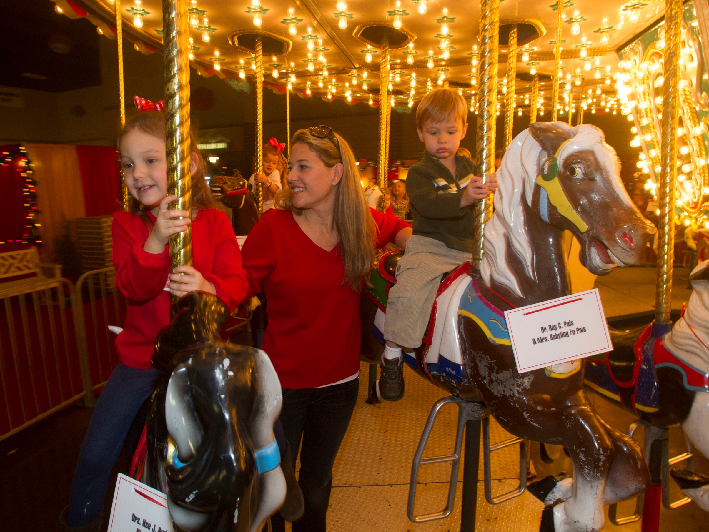 Rebecca Starnes, center and her children Emery, 4, left and Easton, 2 ride the carousel at the Fantasy of Trees.The 28th Fantasy of Trees once again transforms the downtown Knoxville Convention Center into a winter wonderland of decorated trees, gingerbread houses, holiday shops and children's activities, helping move Thanksgiving week into the Christmas season. ( J. MILES CARY/NEWS SENTINEL )