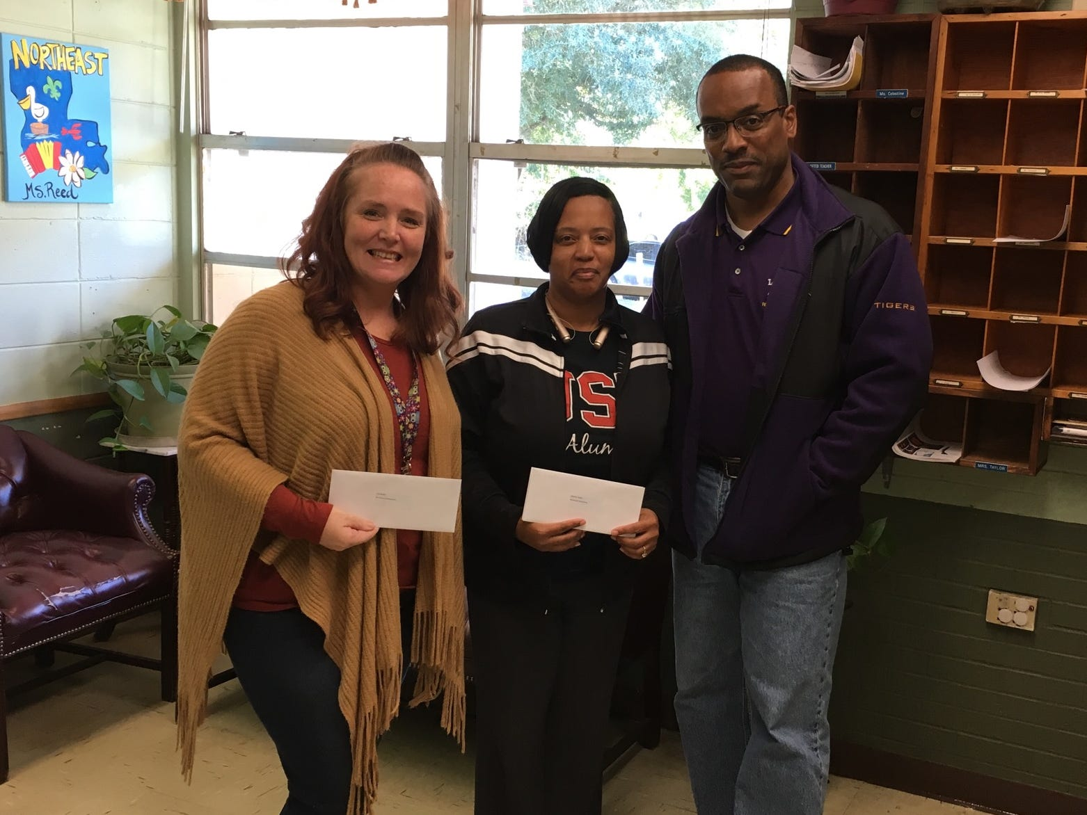 Northeast Elementary School teacher Lisa Miller, left, and Principal Daphne Guillory received a gift card from Herman Fuselier as a part of The Daily Advertiser's Adopt-A-Teacher drive.  Energy Transfer provided a $25,000 donation and Community Foundation of Acadiana assisted in securing gift cards for more than 400 teachers at 134 schools.