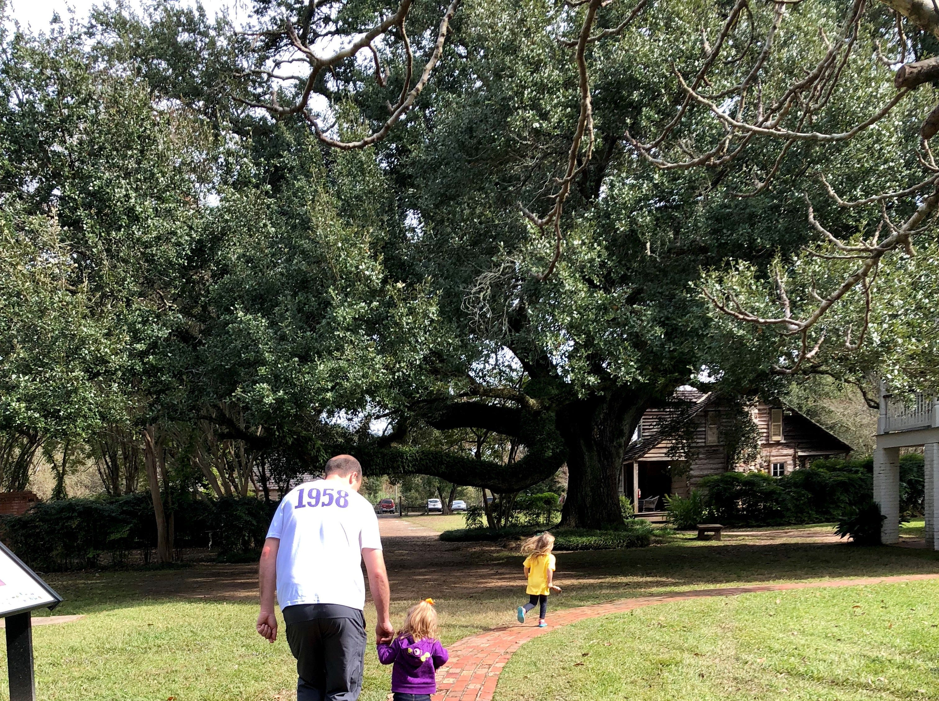 Eric Guidry helps daughters Avery and Marie take the grounds tour of Melrose Plantation in Cloutierville, Natchitoches Parish, as they explore the Cane River Creole National Heritage Trail Nov. 17, 2018.