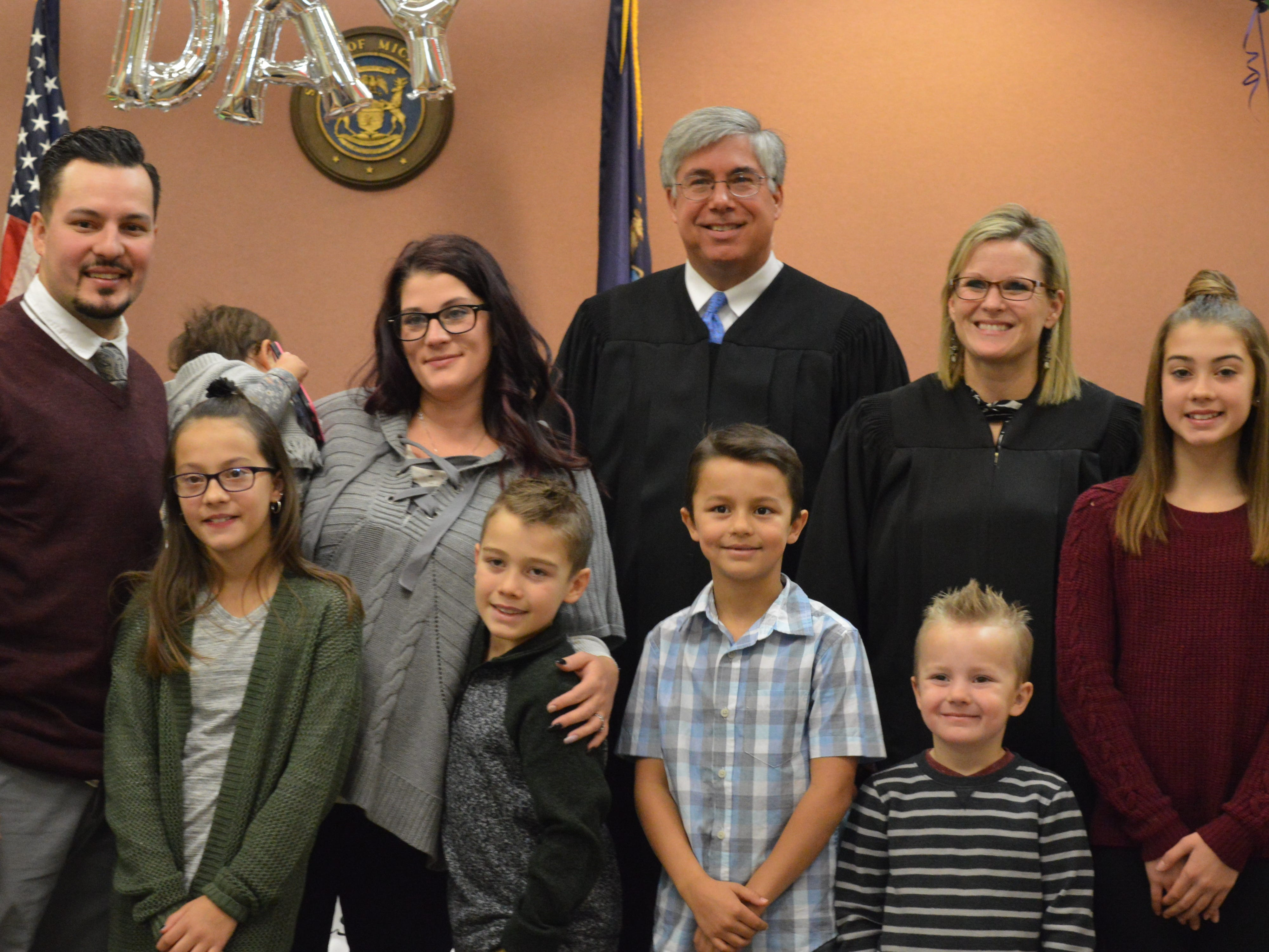 The Eilliot family poses after Rae-lynn and Caiden were legally adopted in Livingston County Chief Judge Miriam Cavanaugh's courtroom on Nov. 20, 2018.