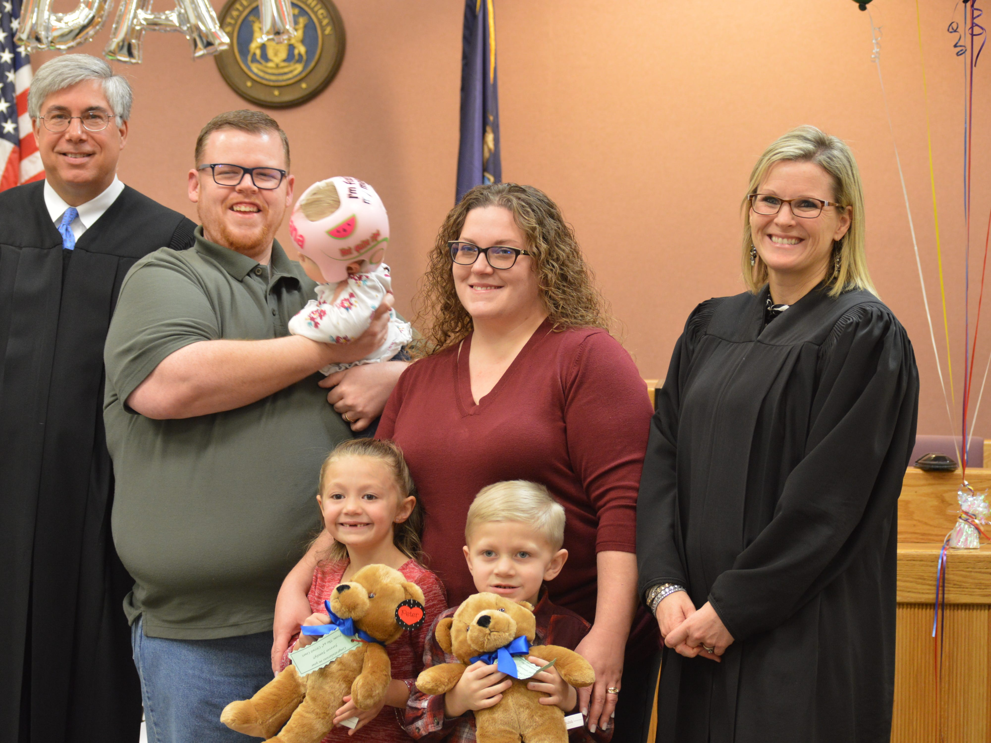 Jeffrey and Erica Poag pose with their two newly adopted children, Angel and Jayden. Livingston County Chief Judge Miriam Cavanaugh and Court of Appeals Judge Christopher Murray finalized adoption on Tuesday Nov. 20, 2018.