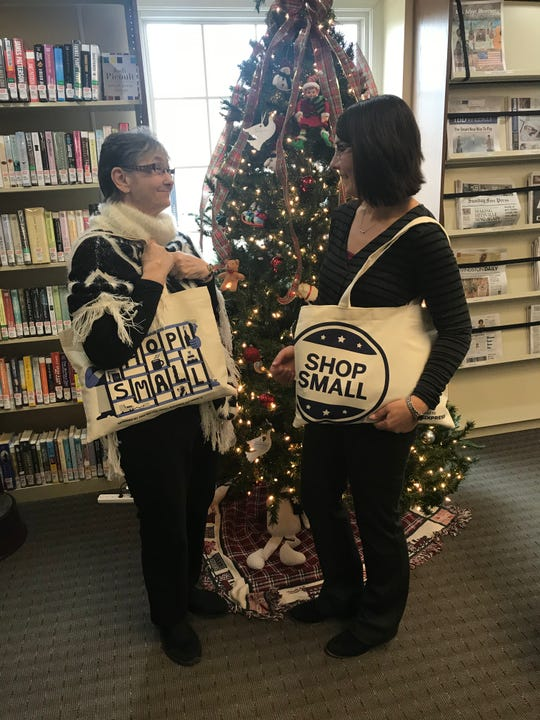 From left, Cromaine District Library's administrative assistant Barbara Rentola and community engagement specialist Stefanie Furge, seen Monday, Nov. 19. 2018, show off some swag bags that will be handed out at the library's Shop Small Saturday pop-up market on Small Business Saturday.