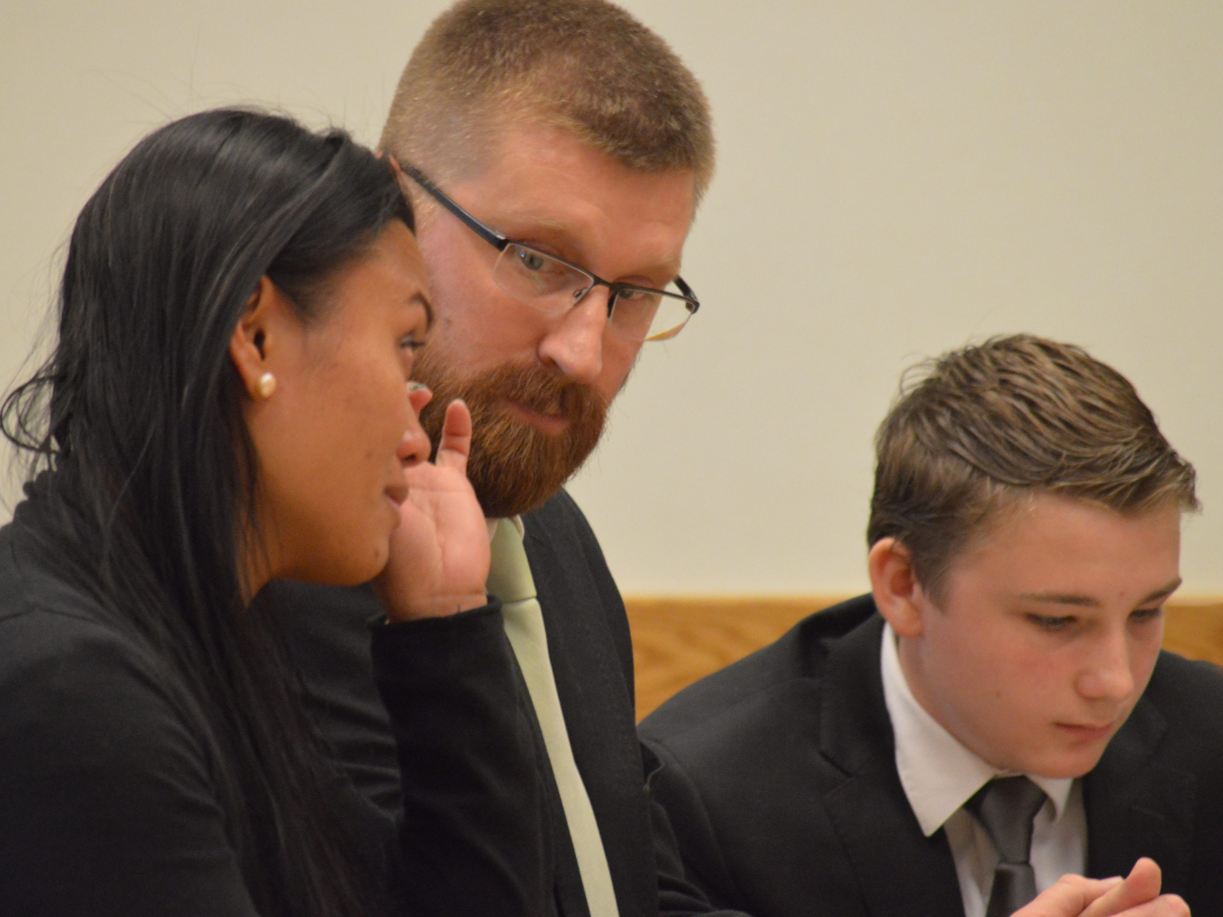 Maris Wallag wipes tears next to her husband Stephen as her son Luke's adoption is finalized on Nov. 20, 2018.