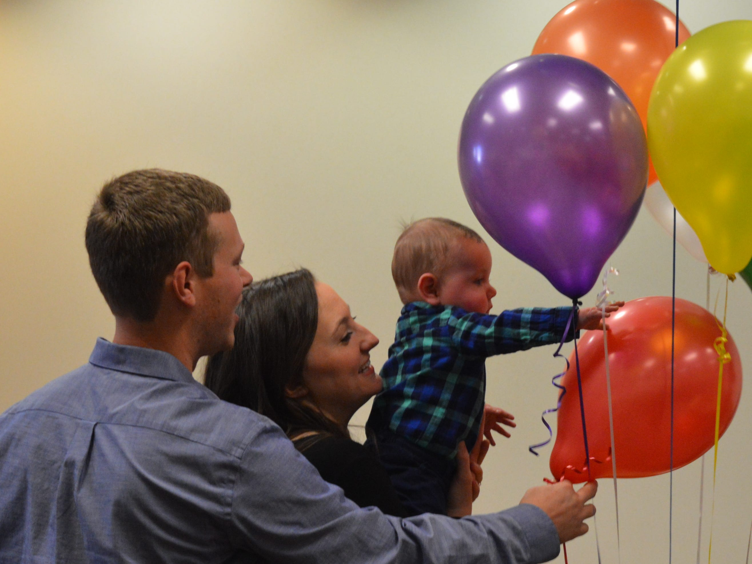 Newly adopted Wyatt Church plays with a balloon after Livingston County Chief Judge Miriam Cavanaugh finalized his adoption on Nov. 20, 2018.