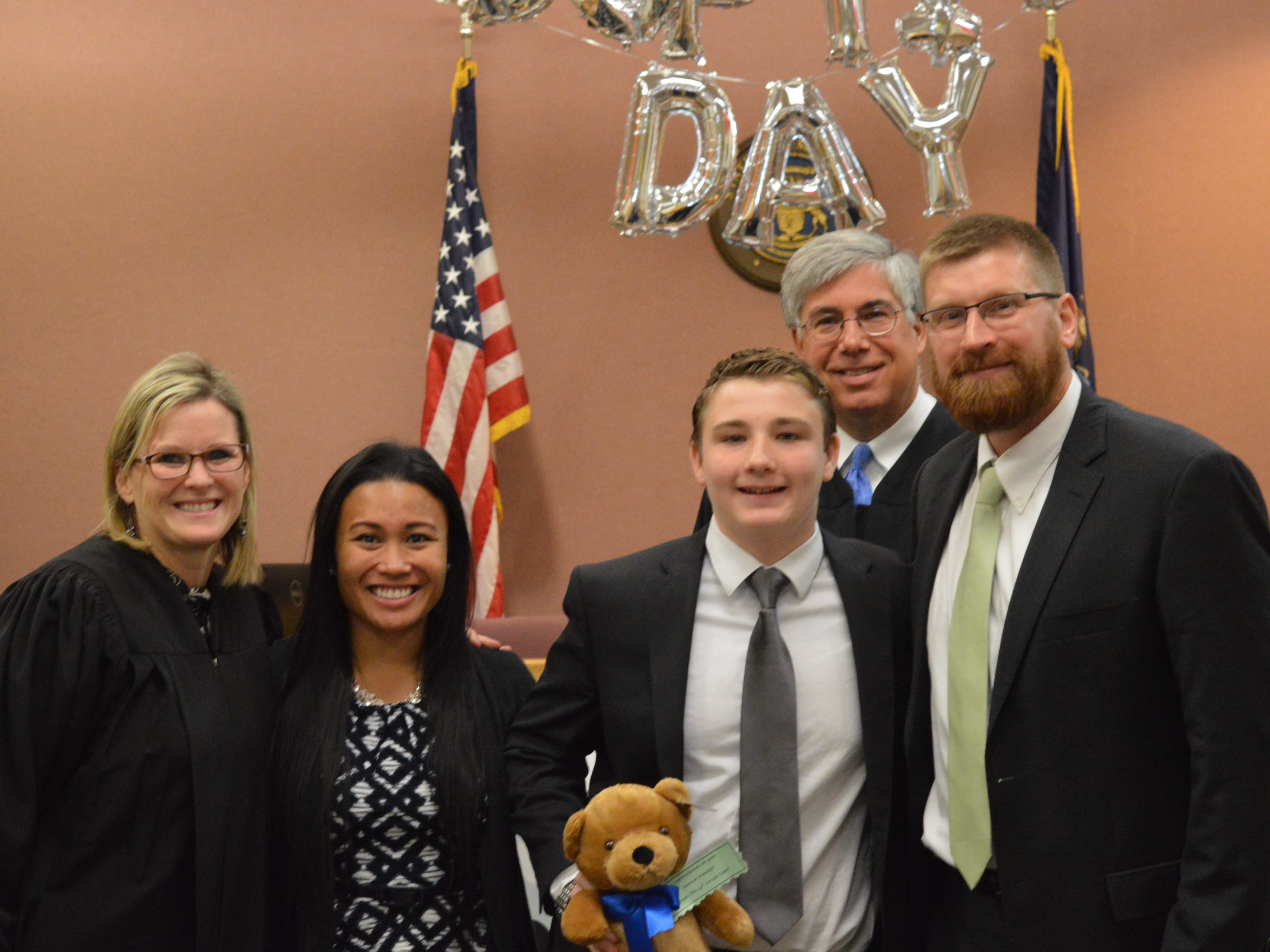 Maris and Stephen Wallage pose with their newly adopted son Luke as well as Livingston County Chief Judge Miriam Cavanaugh and Michigan Court of Appeals Judge Christopher Murray. His adoption was finalized on Nov. 20, 2018.