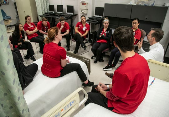 UofL Nursing students listen to assistant professor Paul Clark, RN, talk about their performance in a training drill recently.