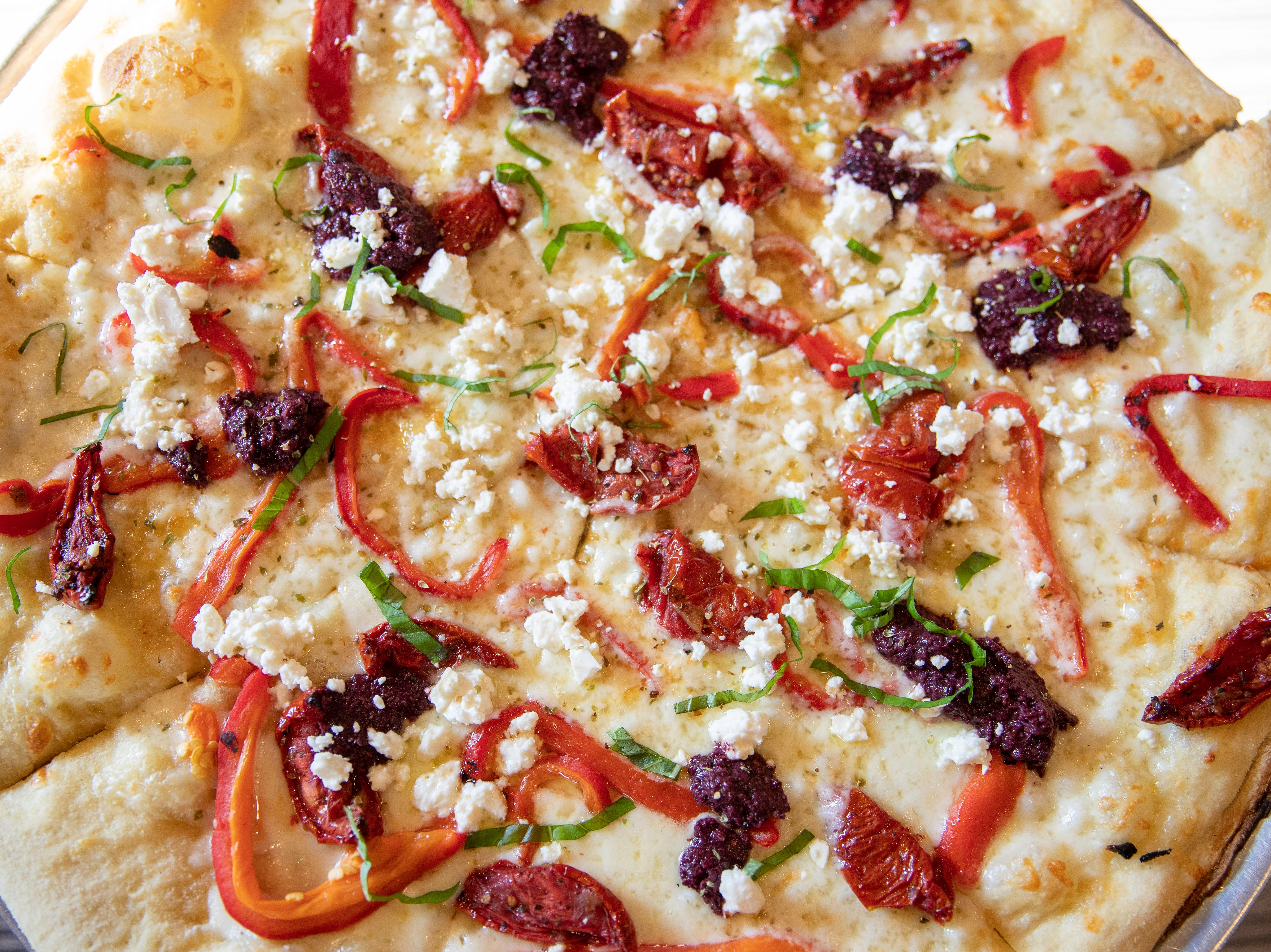 It's All Greek To Me Pizza: roasted garlic butter base, mozzarella & fontina cheese, sun dried tomatoes, roasted red peppers, tapenade, feta cheese, & tzatziki sauce drizzle at Butchertown Pizza Hall, Wednesday, Nov. 7, 2018 in Louisville Ky.