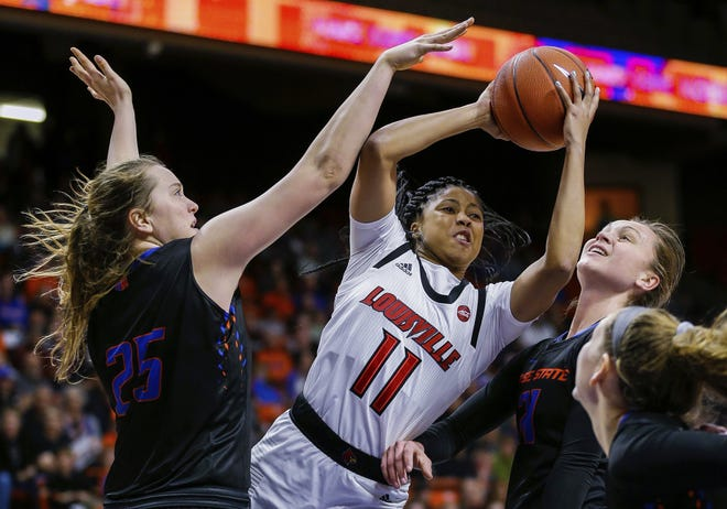 Louisville guard Arica Carter drives between two Boise State defenders. Nov. 19, 2018