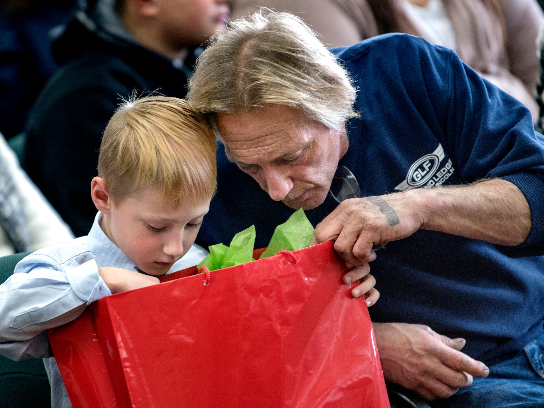 Durwood Fletcher, right, looks through a gift bag with Austin, 7, after his adoption was finalized during a Michigan Adoption Day ceremony at the Clinton County Courthouse in St. Johns. Four families finalized the adoptions of six children.