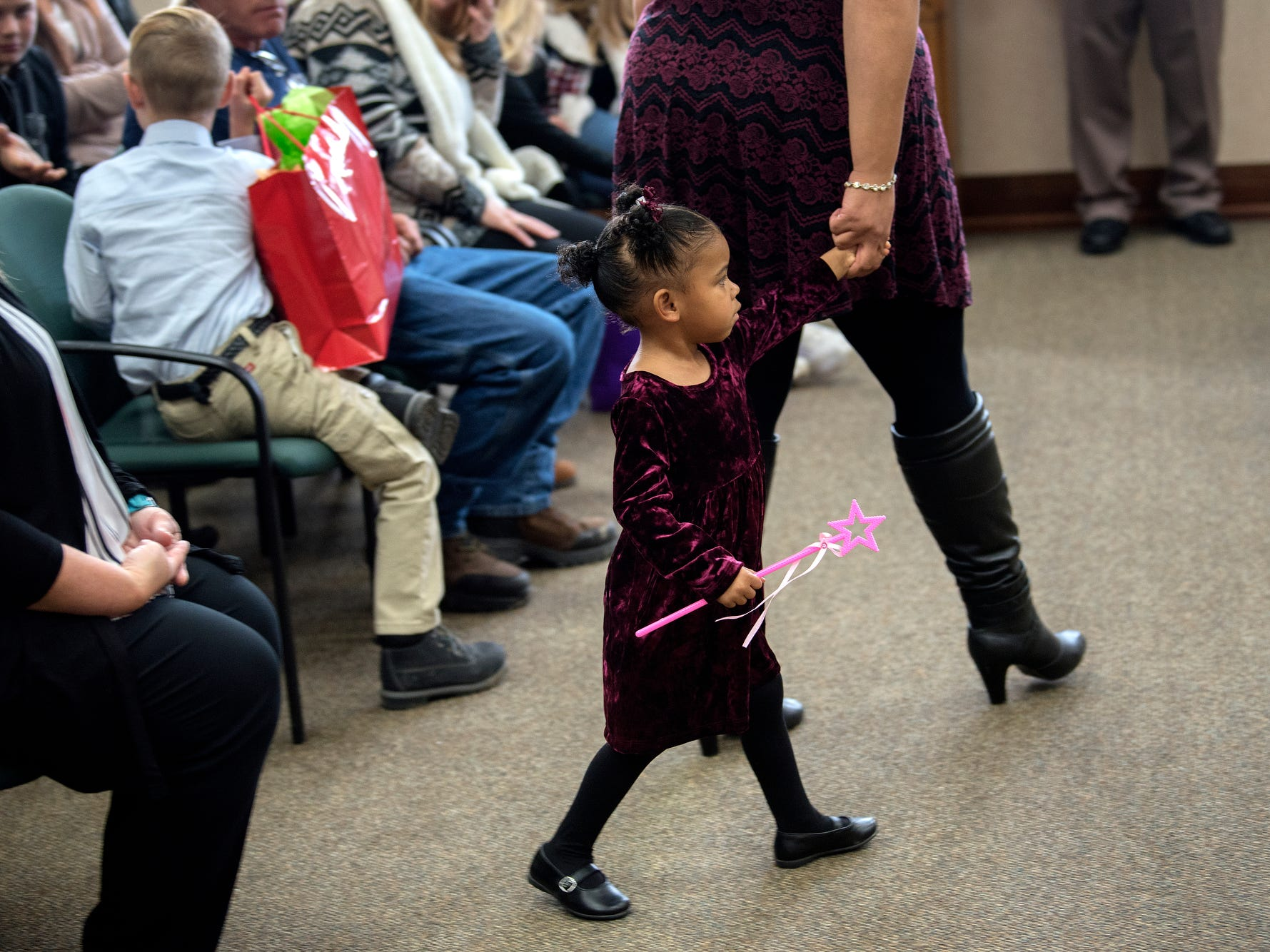 Bath resident Nicole Leggions holds the hand of Azaria, 2, as Nicole prepares to finalize the adoption of Azaria, and her brother Aquan, 2, during a Michigan Adoption Day ceremony at the Clinton County Courthouse in St. Johns. Four families finalized the adoptions of six children.